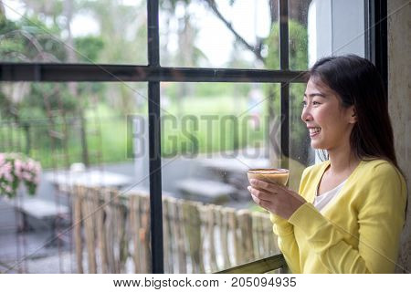 Asian woman is enjoying with coffee break and looking to outside window of coffee shop.