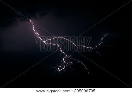 Lightning in the night sky. The concept of bad weather, storms and heavy rain. The power and fascinating beauty of nature