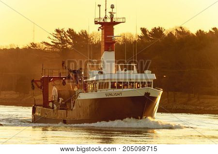 Cape Cod Canal Massachusetts USA - March 4 2007: Fishing vessel Sunlight on Cape Cod Canal in dawn light