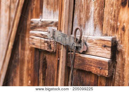 Close-up old simple lock on a wooden door closed with a metal pin rustic latch on an old door made of wood to let nobody in with a rusty metal lock barred old wooden door.