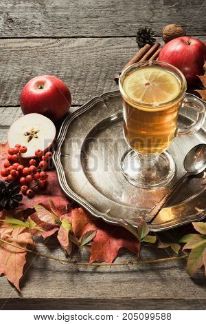 Warming glass cup of tea with a decor of autumn leaves and apples on a wooden vintage board. Fall still life.