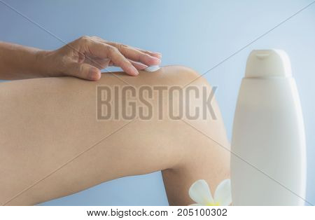 hand of woman apply lotion on skin of knee with lotion bottle on wall background.