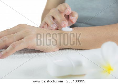 hand of woman apply lotion on skin of her arm with lotion bottle isolated on white background.