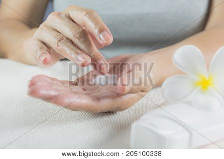 hand of woman apply lotion on skin of hand with lotion bottle on white table.