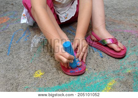 Little girl creatively paints her toe nails with blue sidewalk chalk.