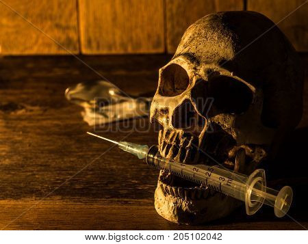 Skull placed on wooden boards. And skull injection syringe The back is medicine Candlelight from the side and a wooden background.