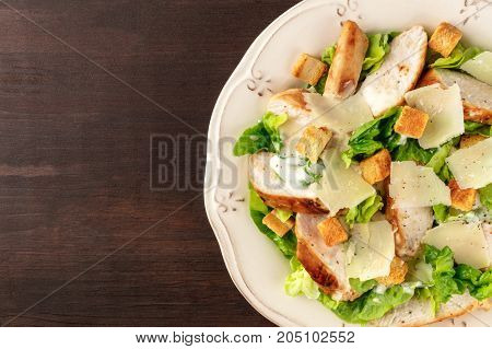 An overhead closeup photo of a plate of chicken Caesar salad on a dark rustic background texture with copy space