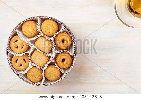An overhead photo of Danish butter cookies and a cup of tea, shot from above on a light background texture with a place for text