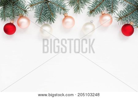 New Year`s card card. Red white balls blue spruce branches on the top of white wooden texture copy cpace