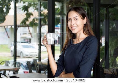 Beautiful young business worker woman drinking hot coffee on break time.