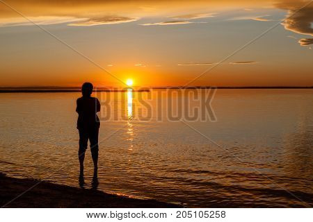 Silhouette of a woman on the beach water's edge watching sunset. Conceptual background image. Silhouette outline modified to render person unidentifiable.