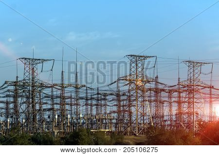 distribution electric substation with power lines and transformers at sunset.