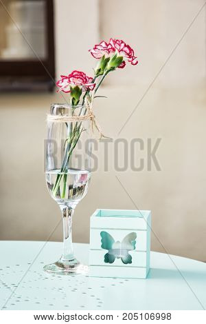 Cut geranium flower with decorative candle on the table in garden restaurant.