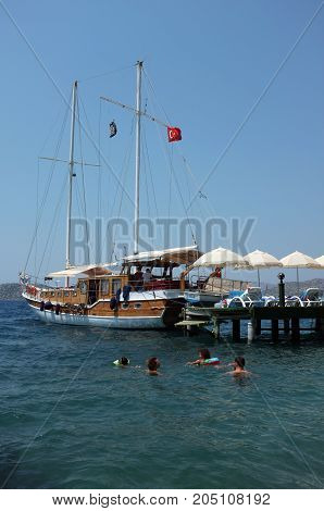 Marmaris, Turkey - August 16, 2017: Family swim near jetty and docked boat during summer holiday in Marmaris, Turkey