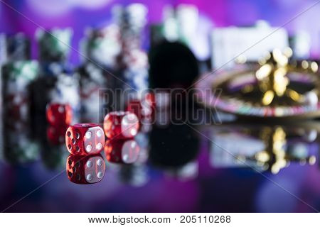 Casino concept. Roulette, cards and dice on colorful bokeh.