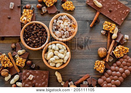 Chocolate with nuts on dark wooden background top view.