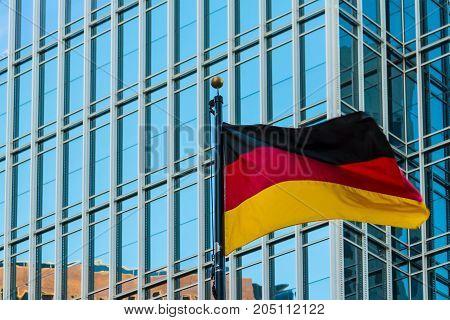 German flag closeup on the background of facade of office skyscraper Atlanta USA