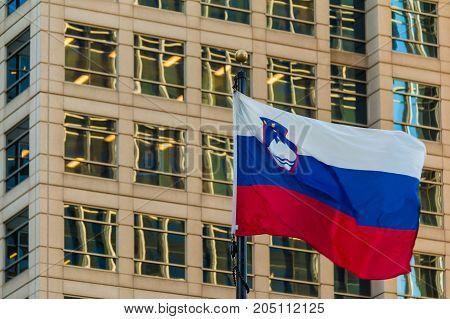 The flag of Slovenia closeup on the background of facade of office skyscraper Atlanta USA