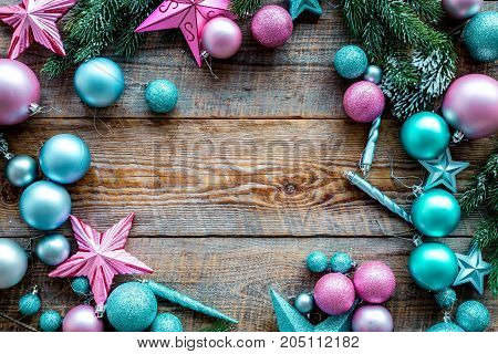 Christmas decoration pattern. Pink and blue stars and balls near pine branches on wooden background top view.