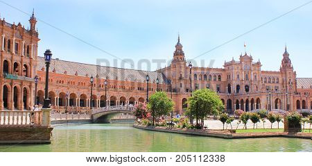 Plaza de Espana (Spain Square) in Seville, main city tourist attraction. Spanish architecture buildings complex with water channel, summer day scene. Famous travel destination in Europe with copyspace