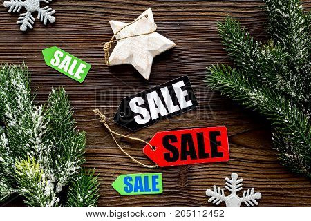Christmas sale. Sale labels near spruce branch and xmas decor on wooden background top view.