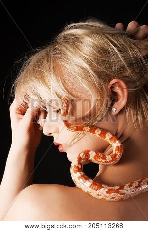Young beautiful sensual woman with snake around her neck; a lot of copyspace available