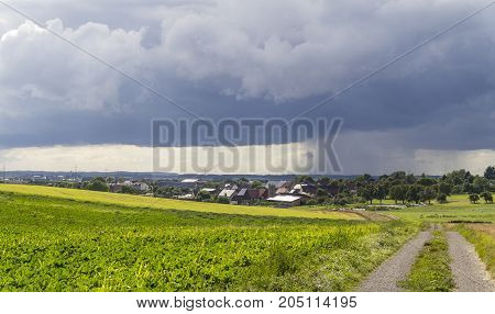 rainy scenery including a small village in rural agricultural ambiance