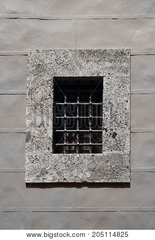 concrete window with thick security metal bars in a grey stone wall prison security protection