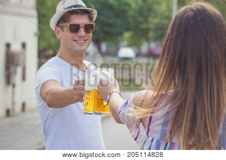 Young modern couple cheering with beer at the city street