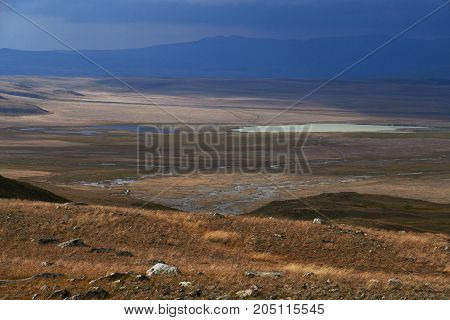 White Cumulus Clouds Come Down From The Mountains, Autumn Landscape In The Steppe. The Ukok Plateau