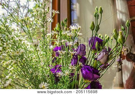 Bouquet of purple flowers Lisianthus with branches delicate white wildflowers on the windowsill in bright sunny day