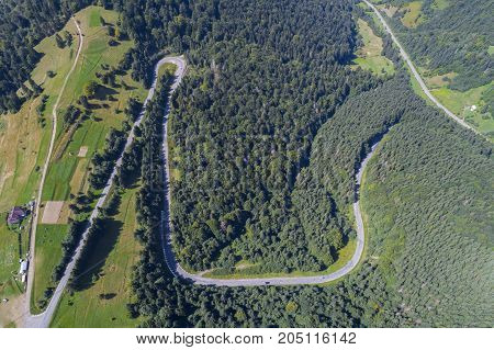 Aerial view over mountain road going through forest landscape. Top view of picturesque winding road among the pines and lawns.