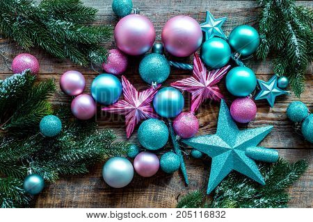 Decorate the christmas tree. Pink and blue stars and balls near pine branches on wooden background top view.