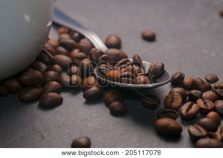 Coffe beans on a spoon on gray rock background