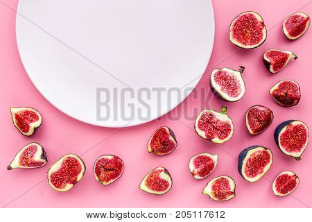 Empty plate among fresh blue figs on pink background top view .