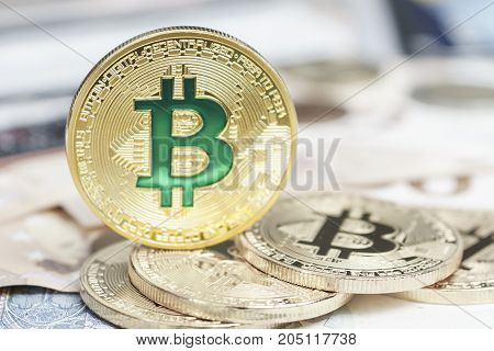 Cryptocurrency physical green bitcoin coin and the euro money.
