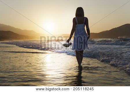 A girl is walking along Crete island coastline at the sunset time.