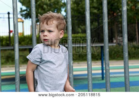 Serious Child On Fence Background