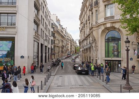 Paris; France- May 01; 2017: There are people walking along the Champs Elysees and Bossano Street. Along the sidewalks are cars