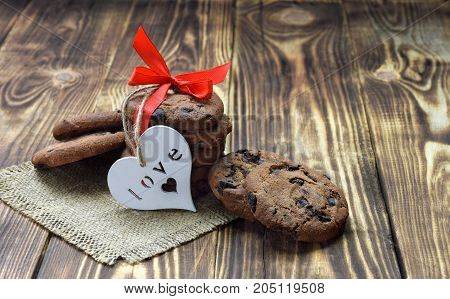 Lovely delicious gift. Chocolate cookies with red ribbon  on wooden background.  Comfort / Love / Holidays / Caring. Rustic style.