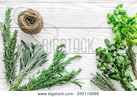 fresh herbs and greenery for spices and cooking on white wooden kitchen desk background top view mock up