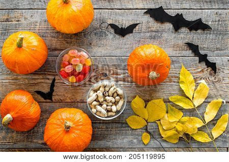 Halloween background. Pumpkins, paper bats and autumn leaves on wooden background top view.
