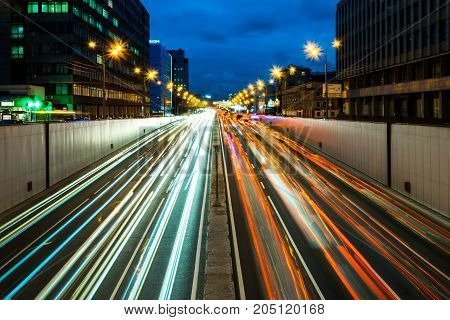 Busy street in the city at dusk, full of car light streaks dynamic blue hour shot with long exposure motion blur effect