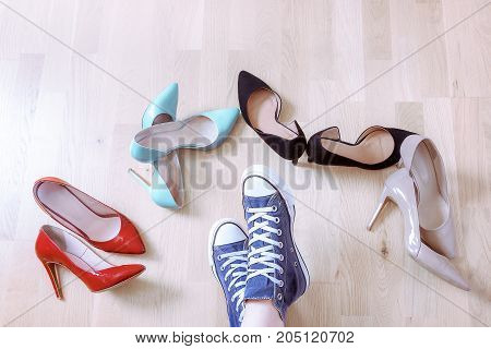 Conceptual image with a girl's feet wearing sneakers while surrounded by elegant high heels shoes. Choosing comfort over elegance.