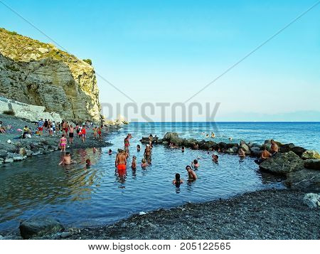 Agios Fokas, Greece - August 02, 2015: In the evening, many people take a bath in the Embros thermal baths (Embros Therma), a thermal spring of 49 °C, which flows from a crevice.