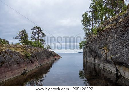 The strait between two stone islands in a large lake. Trees grow on rocks.