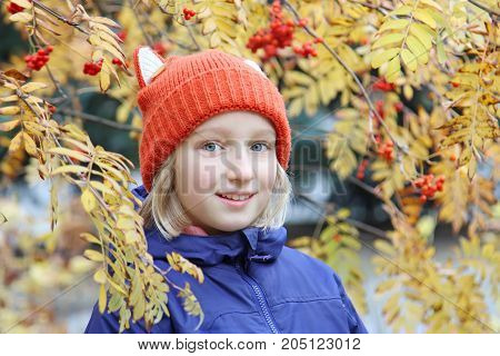 Cheerful girl smiling, the child is dressed in a funny knitted Cheerful kid girl smiling, the child is dressed in a funny knitted warm hat with ears, looks like a fox. Autumn, outdoors portrait with yellow leaves and rowan berries.
