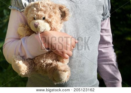 Lonely girl holding a teddy bear as of her best friend