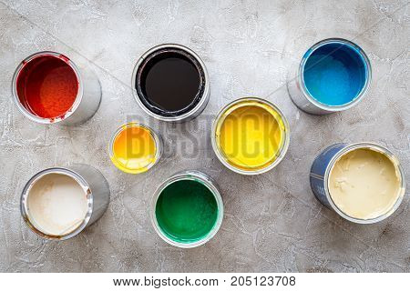 Paints in tin banks on grey stone background top view.