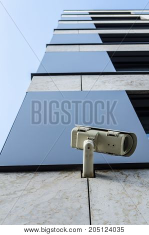 surveillance monitoring security camera on a house corner with blue sky